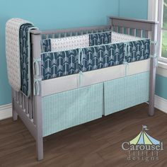 Crib bedding in Aqua Herringbone, Navy and White Arrow, Silver Gray Antlers, Silver Gray Linen. Created using the Nursery Designer® by Carousel Designs where you mix and match from hundreds of fabrics to create your own unique baby bedding. #carouseldesigns