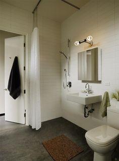 Bathroom with white tile walls, concrete floors, exposed light fixture, shower.