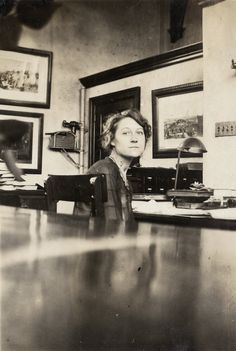High Park Branch - Toronto Public Library. Vintage photo circa 1920s of female librarian / staff behind checkout desk on adult floor.  Notice the early fire hose equipment in the background - early health and safety fire protection in libraries.