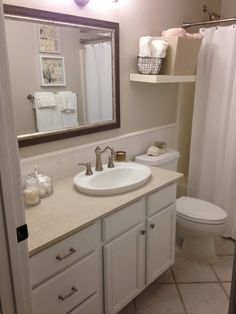 A crisp and bright coastal bathroom makeover featuring a quartz countertop, subway tile backsplash, vintage-look faucet, and clean white accessories, all DIYed.