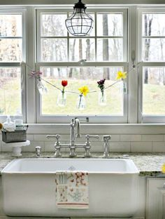 We are utterly obsessed with blogger Courtney's idea to hang a small bottle garland in front of her farmhouse sink. Click through for more spring decor ideas.