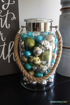 Peacock blue, green, silver and gold ornaments in a glass vase. Great Christmas decor idea!
