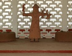A standing traditional sculpture after the ancient themes and stylization of an Oba. The statue stands against a modern wall screening consisting entirely of sunshading breeze blocks. Behind these is the traditional wall washed in traditional white chalk with its characteristic pattern of horizontal ribbed indents. Ancient Artefacts, Traditional Sculptures, White Chalk, Modern Wall, Breeze, Palace, Statue, Architecture, Pattern