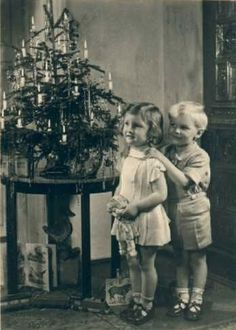 Two precious children pose next to table top Christmas tree.