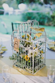 vintage birdcage centerpieces double as table numbers. Love the little birdies on top!
