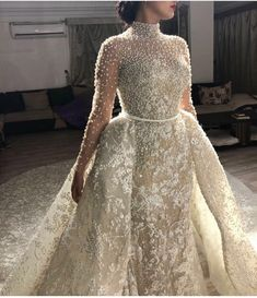 This pearl beaded #bridal gown has a detachable over skirt. The lace and embroidery detail on this #fashion piece has beading as well. #Hautecouture #dresses like this do not have to cost you a fortune. You can get the same look for less from our firm. We are in the #USA and offer custom #weddingdresses and #replicas of couture designs to brides on a budget. So if what you want is not in your range we can surely help.
