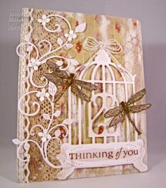 Simply Southern Sandee: Spellbinders birdcage and some dragonflies. I cut out the sentiment with a Spellbinders die. I added glossy accents to the birdcage, sentiment, and the dragonfly bodies. The wings have stickles on them. Added the bow made with Becca's Peg Bow Maker and the small Cheery Lynn Flourishes. Then I added Martha's tiny hydrangeas and pearls to complete the card! more...>