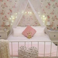 floral wallpapered room with canopy and fairy light adorned white bed!! i love it