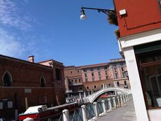 lamp hanging enlightens the view of this picture capturing the clear blue sky among the pastel buildings