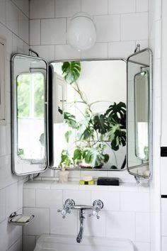 ビンテージの壁掛け三面鏡のある白いタイル貼りのバスルーム