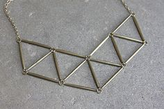 Prisms and geometric designs are in this season, and this necklace will instantly make any outfit look modern and hip! This eye-catching geometric choker will elevate your casual outfit or complement a classy one. Its great for a day at the office, or right at home with a sundress.  Catch compliments left and right with this statement piece.