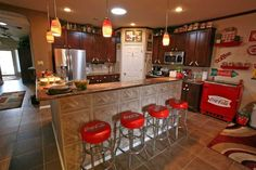 Coca-Cola memorabilia decorates the kitchen; four barstools offer seating at the L-shaped granite bar; the husband refurbished the metal cooler next to the cabinet; itÕs used for storage since it lacks a compressor.