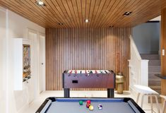 Oak slat wood wall and ceiling add warmth to this #basement