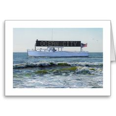 """A nautically nostalgic note card by the award-winning artist Paul McGehee. This scene from the 1980's shows Ocean City, Maryland's original """"sign boat"""" slowly making its way up the coastline, just off of the beach. Bathers at the shore would be entertained by the animated sign which promoted Ocean City events as well as specials at the local restaurants, bars, dance clubs, etc. This scene brings back fond memories of carefree days at the beach. Each card comes with envelope."""
