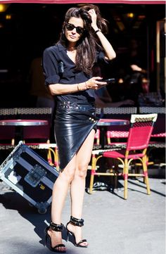 A black silk blouse is worn with a leather wrap skirt, strappy heels, and Ray-Ban wayfarers