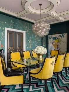 With hints of art deco style, this dining room is wild and wonderful. Gorgeous teal floral wallpaper, a soft lavender coffered ceiling, bright yellow velvet chairs, a funky bubble chandelier and a colorful chevron rug pull the unique look together.