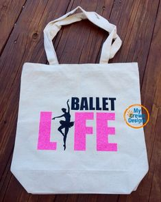 "Our Ballet Life Tote is the perfect gift for any ballet dancer or teacher. Show up to your recital in style with our 13.5x13.5 Ballet Life Tote Bag! Color customization available for the ""Ballet Life"""