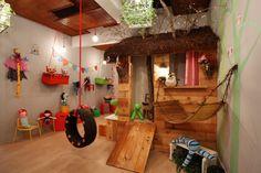 Uma casinha bem lúdica feita com tábuas de madeira, árvore com coruja pintada na parede com direito a uma rede de bambuzinho, balanço de pneu, bandeirinhas de tecido, muitos brinquedos espalhados pelo chão e um lugar reservado para a arte com bancada para pintar e depois pendurar a obra no varal. Ele vai amar!!