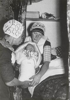 Grootmoeder overhandigt het ingebakerde kind aan de moeder in de bedstede. ca 1940 #Utrecht #Spakenburg
