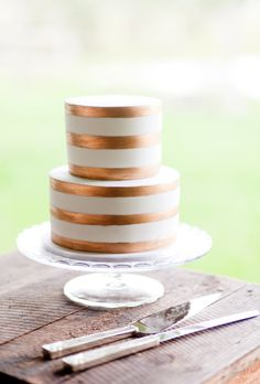 Brides.com: 29 Glam Metallic Wedding Cakes A two-tiered wedding cake with bronze stripes, from Ideas in Icing.Photo: Karen Buckle