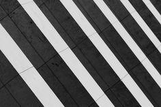 Lijn: Op de foto staan balken van een gebouw. Met een contrastrijk afgesneden diagonale compositie overlappen de verschillende balken elkaar.