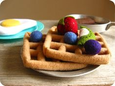 Here's a different idea for felt waffles-- it looks like the ridges are created by rolling up some felt into a tube and laying the tubes out to make the grid.  Not sure how they're attached...maybe glue?  Maybe hand tacking?