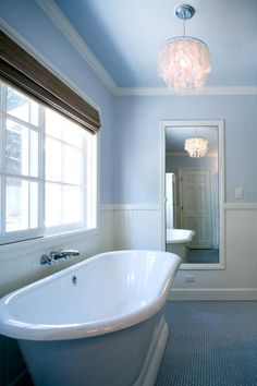 This blue and white bathroom features a contemporary soaking tub with a wall-mounted faucet. Blue penny tile adds texture while coordinating with the tub and painted walls and ceiling. White beadboard adds a vintage touch and keeps the blue from overwhelming the space, while a large window and capiz shell light make for a bright and inviting space.