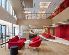 Communal work areas and privacy pods are dispersed throughout the non-linear space, which is punctuated with raspberry-coloured furniture, walls and carpeting. The bright hue is paired with black-and-white checkered carpeting, and wood flooring and wall panels.