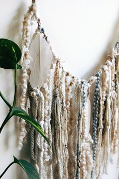 One-of-a-kind home decor by Golden Hour Studio. This unique garland is little in size but packed with beautiful details. This garland style wall hanging is strung on thick twine, and features a blend of luxurious yarns in natural colors and ivory, with some strands of a delicate grey-blue. Three preserved ivory feathers hang throughout, accented with pearls. Two hand tied yarn tassels in an oatmeal color hang between the feathers. This piece is on a smaller scale so that you can conveniently…