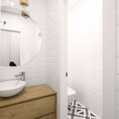 Reforma de vivienda en el barrio de Salamanca (Madrid). Baño con suelo hidráulico bicolor en blanco y negro de motivos geométricos, azulejo metro en paredes y lavabo sobre encimera con mueble de madera y espejo circular. Proyecto de R de Room.