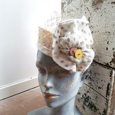 Knotted straw pill box hat with net trim and veiling.