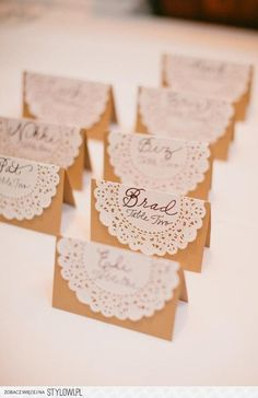 Doily seating chart as cards on string attached to cork board.