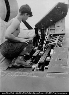 Marine Pfc C.H. McClure servicing the three Browning M2 .50 caliber machine guns in the right wing of an F4U-1 Corsair fighter on Bougainville 9 December 1943.