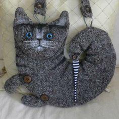 Kočkotaška 3/9 Taška ve tvaru stočené kočky z vlněného úpletu, vel.30*33cm, délka ucha 70cm, otvírá se na zadní straně zipem, je vyložená kvalitní bavlněnou podšívkou s tiskem.