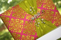 Glamourous green guestbook. We can't get enough of this pretty guest book! Not only is it wrapped in this year's hottest color, but the bead work is gorgeous! Made with a pink and green damask fabric this guest book is centered by a coordinating green polka dot fabric and a beaded brooch.