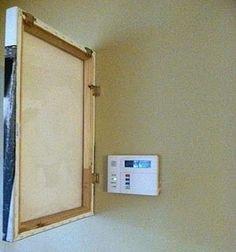 Cachez votre thermostat en accrochant un tableau à votre mur avec des charnières.
