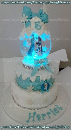 "Frozen Light Up Snow Globe Cake. 8"" & 6"" round chocolate sponge with chocolate buttercream filling. Covered in blue & white sugar paste. White royal icing snow detail. White flower paste snow flakes. Blue flower paste bow. Diamanté trim detail. Handmade glass snow globe dome with frozen figures & colour changing light up base. Snowflake decorated cake board."