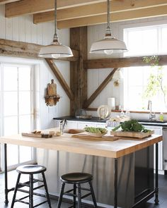 A rustic and refined barn home features crafted pendant light fixtures in the kitchen from old metal shades and gas-pipe fittings. The island counter is…