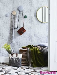 Scandinavian inspired hallway decorating idea: Embrace hygge-style, feel-good fabrics, soothing colours and natural materials. Contrast an aged plaster-effect textured wallpaper with rustic seating, sumptuous flooring and huggable textiles. (Photographer: Caroyln Barber). Find more inspiration at housebeautiful.co.uk