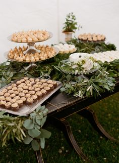 This dessert table was all but hidden with an assortment of leafy green garlands, which swirled around platters of cupcakes and a single tier wedding cake.