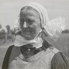 Vrouw uit Giethoorn met gehaakte opknapmuts. Deze mutsen werden door bepaalde vrouwen in Giethoorn gemaakt. De bodem van de muts kwam oorspronkelijk uit Kuinre, waar vissers ze knoopten. Deze muts is door de vrouw geheel zelf gemaakt. De witte katoenen keelbanden hebben aan het uiteinde een bewerkt strookje. 1947 #KopOverijssel