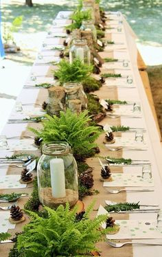 Top 23 Remarkable Rustic Wedding Centerpieces---mason jars, green foliage and candles on the burlap table runner at an outdoor reception for winter.