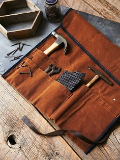 Orville Leather Tool Roll | Handmade in America, this waxed canvas tool roll is made of sturdy tan waxed canvas with blue trim accents. Featuring 10 pockets, perfect for storing all rugged tools of the trade. The top flap folds over and rolls around, with a leather tie for safe keeping.