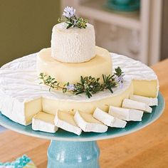 "Easy DIY hors d'oeuvres: Cheese ""Cake."" This pretty centerpiece made of wheels of cheese is drop-dead easy. Choose pretty flowers and herbs in season—lavender would be perfect. Serve with your favorite crackers or French bread rounds."