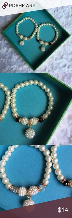 PEARL CRYSTAL ELASTIC BRACELET Classic elegance. Slide these right on at any age to polish off your look. Both bracelets have gold accents. One has iridescent beads and the other one black. Smaller clusters of pearls hang from the bracelet giving it a slight upgraded look from a band only. Fits 7-8+ -No trades. 51twenty Jewelry Bracelets