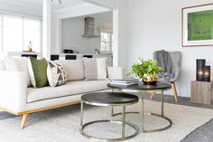 open plan living ideas, textured rug, round black and gold coffee tables, neutral sofa with pops of colour