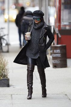 Vanessa Hudgens in a black turtleneck sweater, over-the-knee boots, moto jacket, and newsboy cap in NYC