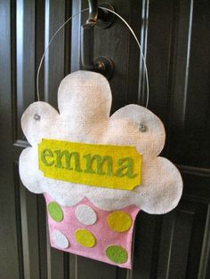 """Burlap Door Hanger. Did it! I made something quite similar out of felt for my daughter's 1st (cupcake themed) Birthday party. I hot glued (could have sewn--lazy...) buttons to the top for """"sprinkles"""" and didn't put a name on it. I hung it on the front door."""