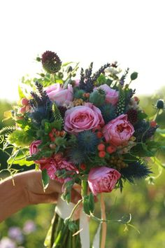 Bridal bouquet with english garden roses, sea holly, poppy pods, drumstick alliums, sweet pea tendrils, hypericum, bells of Ireland, stock, viburnum berries and lavender.