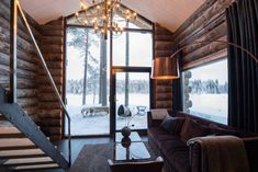 Stay in a Swedish authentic luxury Lapland lodge with 2 traditional log cabins on the edge of the river surrounded by the scenic forest landscape